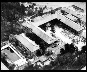 第1次改築前の木造校舎(広場中央にお手植えの松;昭和31年頃)